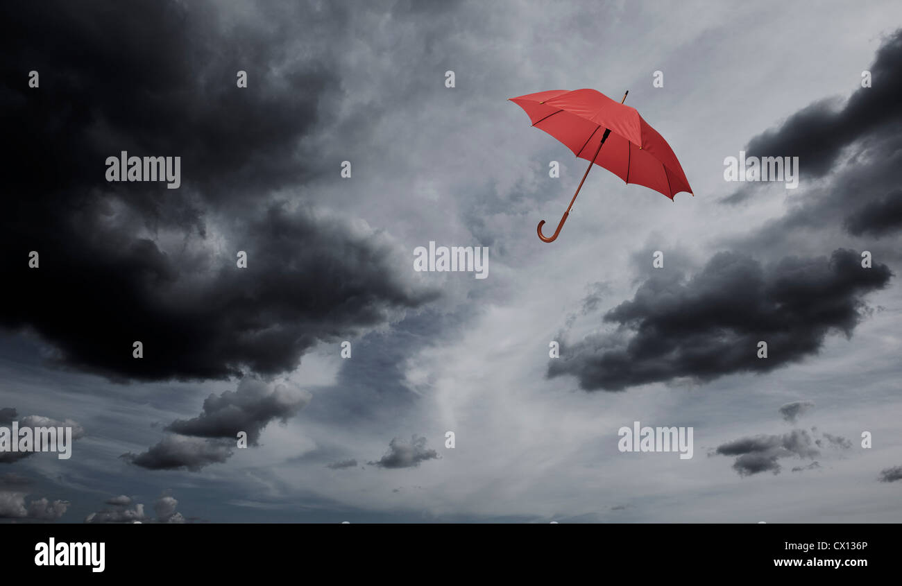 Red umbrella floating through cloudy sky Stock Photo