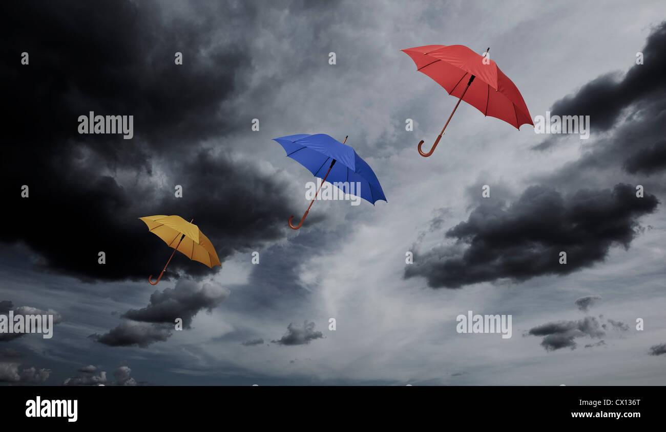 Three umbrellas floating through cloudy sky - Stock Image