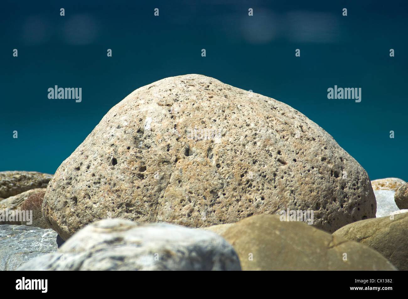 Close-up of a big pebble on a pebble beach with the blue sea in the background Stock Photo