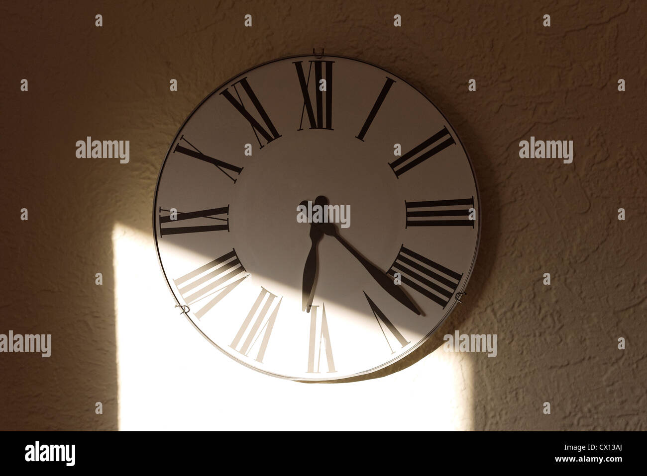 Sunlight and shadow on a traditional clock face - Stock Image