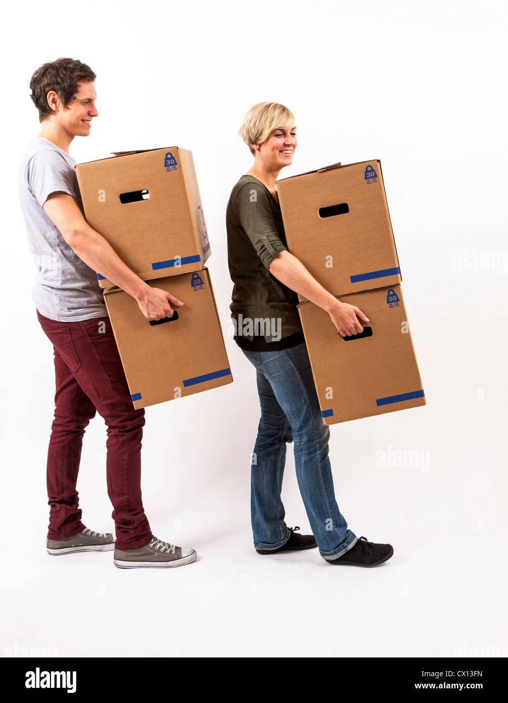 Symbolfoto Umzug, Auszug, umziehen. Junges Paar trägt Umzugskartons. Umzugskisten aus Pappkarton. Stock Photo
