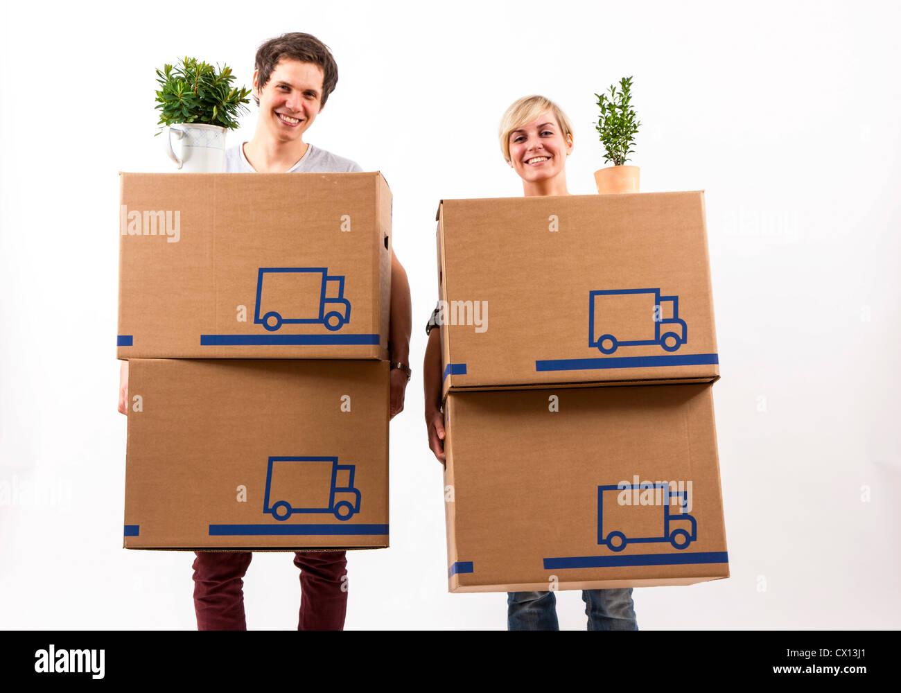 Symbolfoto Umzug, Auszug, umziehen. Junges Paar trägt Umzugskartons und Zimmerpflanze. Umzugskisten aus Pappkarton. Stock Photo