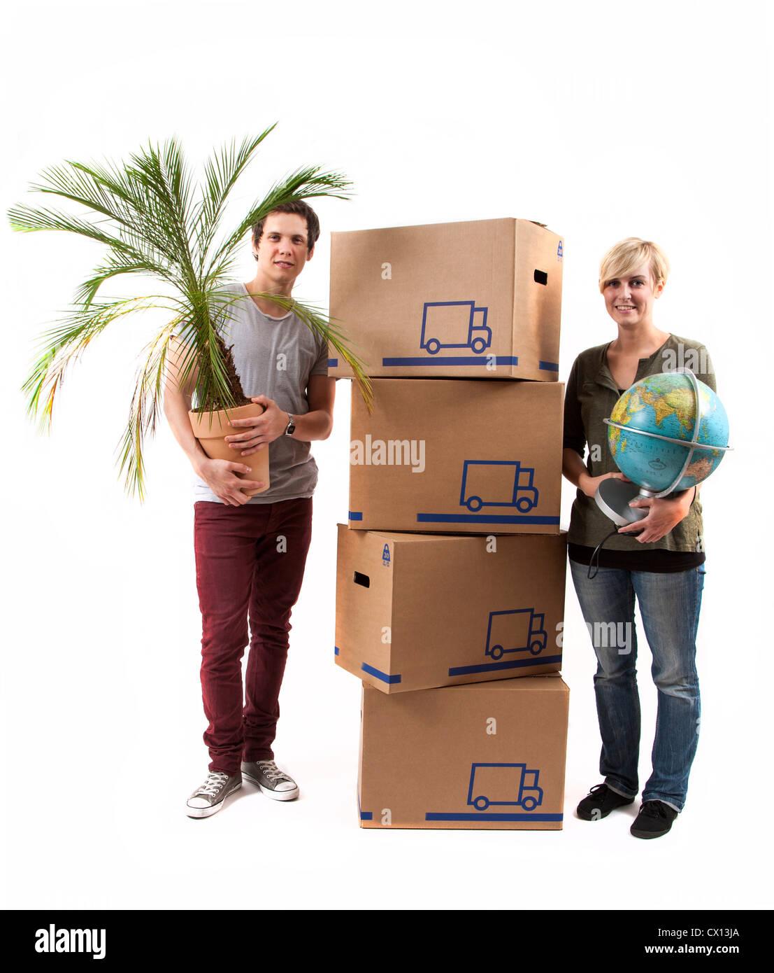 Symbolfoto Umzug, Auszug, umziehen. Junges Paar mit Umzugskartons Globus und Zimmerpflanze. Umzugskisten aus Pappkarton. Stock Photo