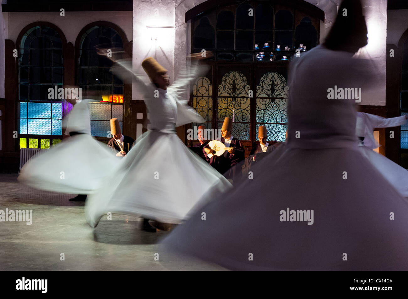 Whirling dervishes perform to visitors in the event hall of Sirkeci Train Station on October 21, 2005 in Istanbul, - Stock Image