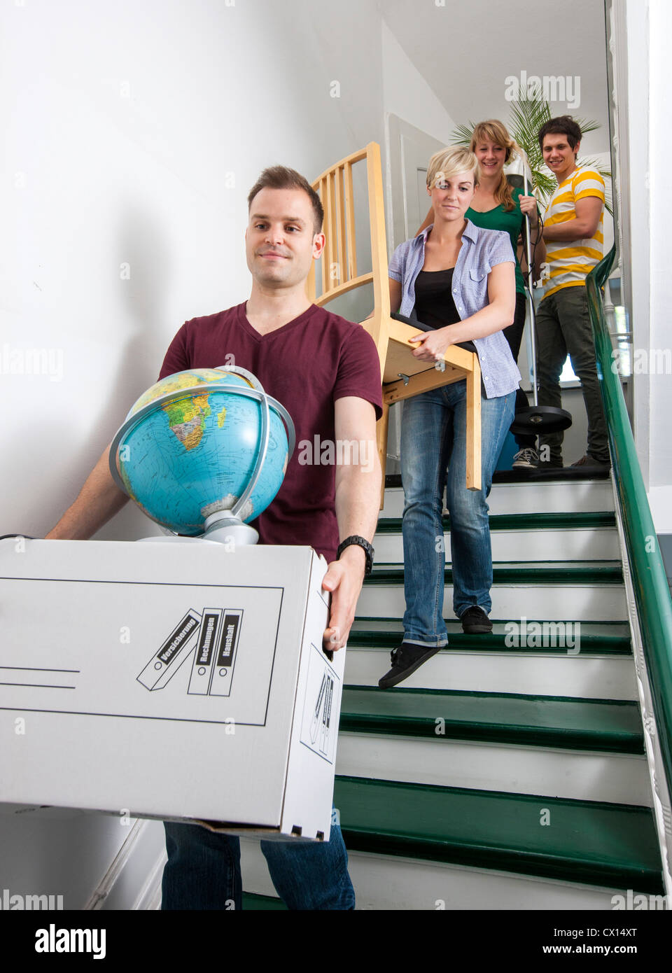 Young people moving in to a new apartment. Friends help carrying moving boxes, furniture and things upstairs to Stock Photo