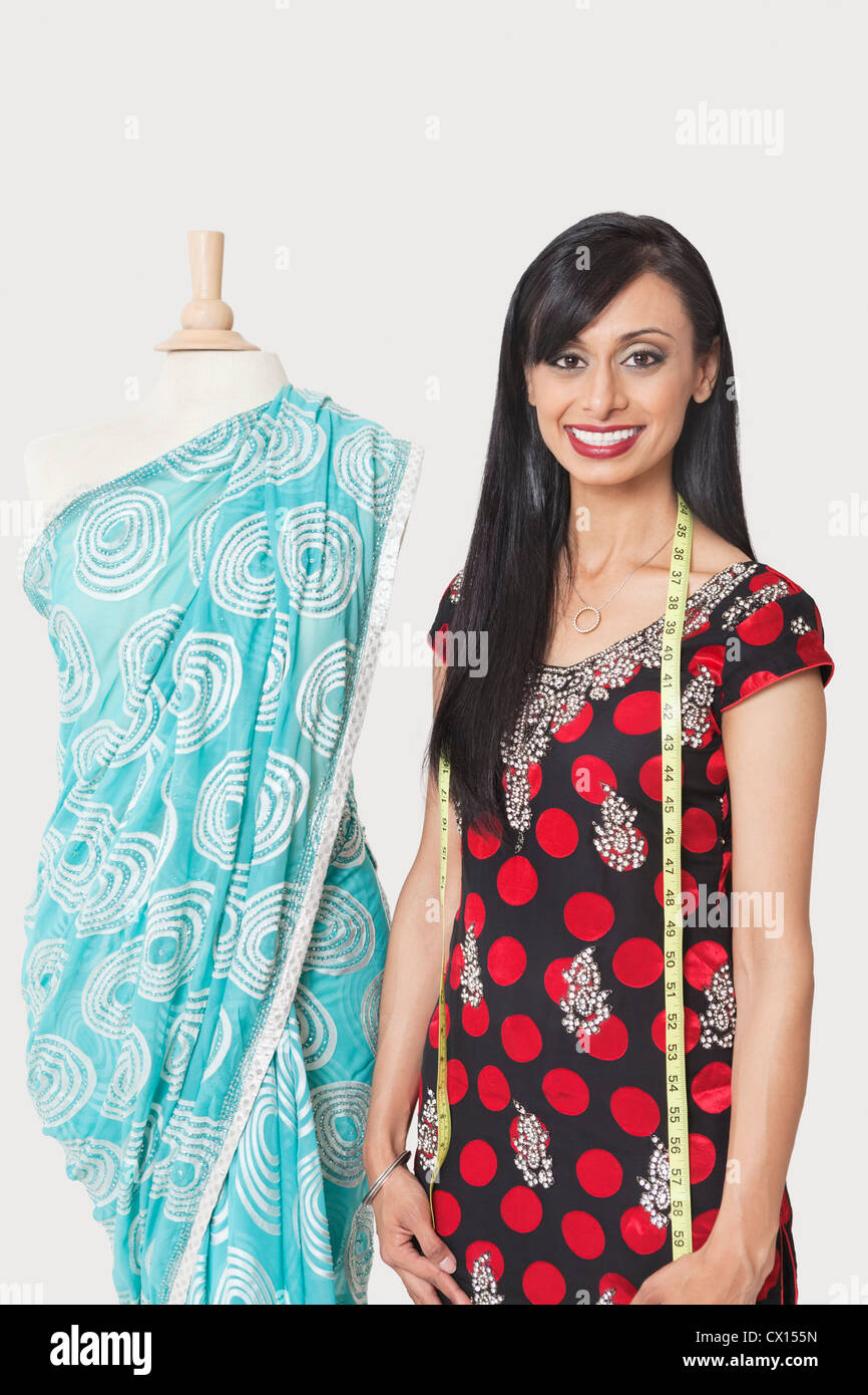 Portrait of happy Indian female fashion designer standing by dummy draped in a sari Stock Photo