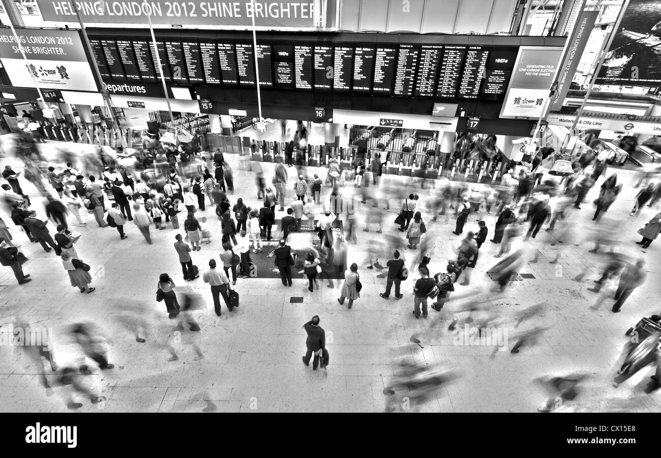 An interesting perspective showing a static, stationary commuter watching the board at Waterloo Station in London. - Stock Image