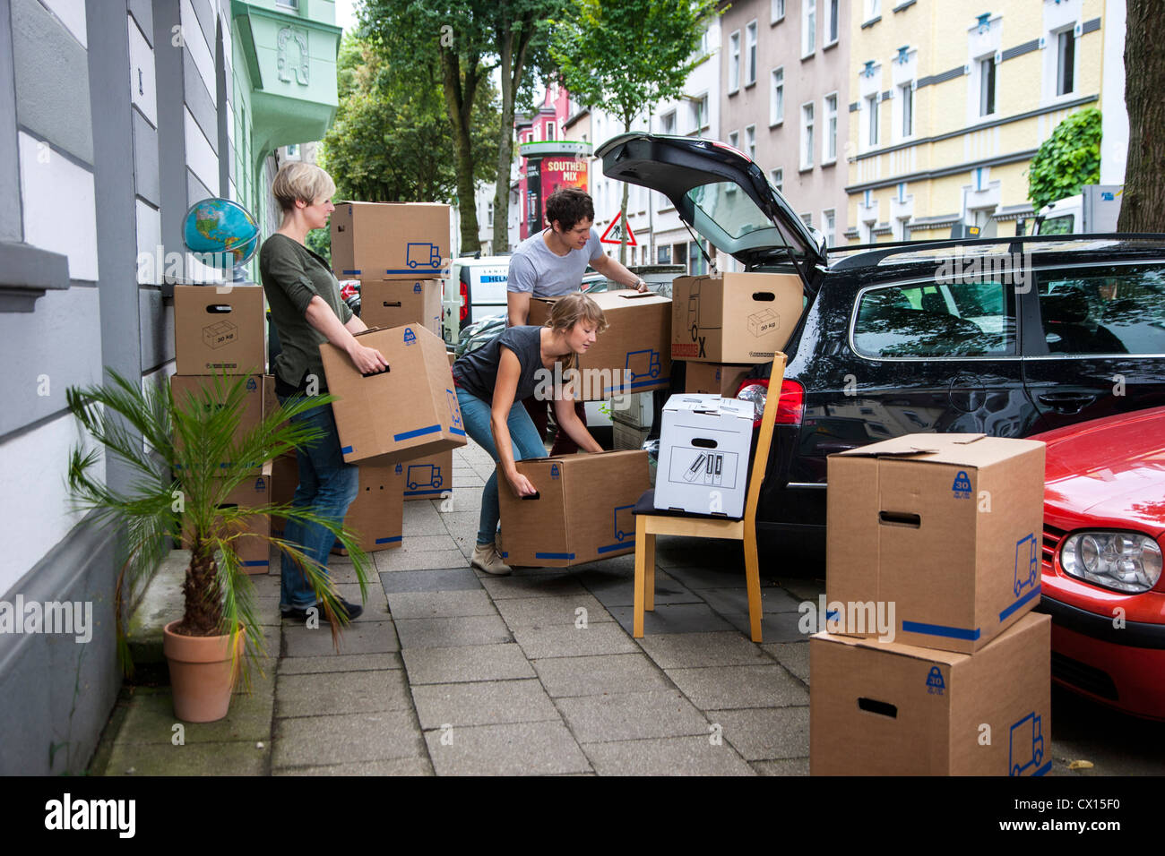 moving into a new apartment friends help carrying moving boxes stock photo 50428084 alamy. Black Bedroom Furniture Sets. Home Design Ideas