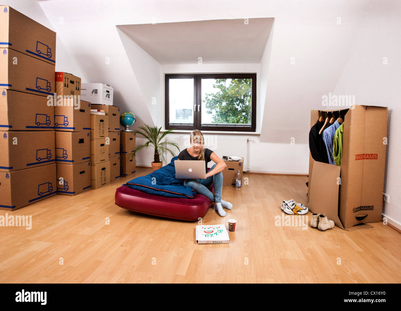 New apartment furniture Urban Young Woman In Her New Apartment Still No Furniture Living Out Of Moving Boxes Works With Her Laptop Computer Alamy Young Woman In Her New Apartment Still No Furniture Living Out Of