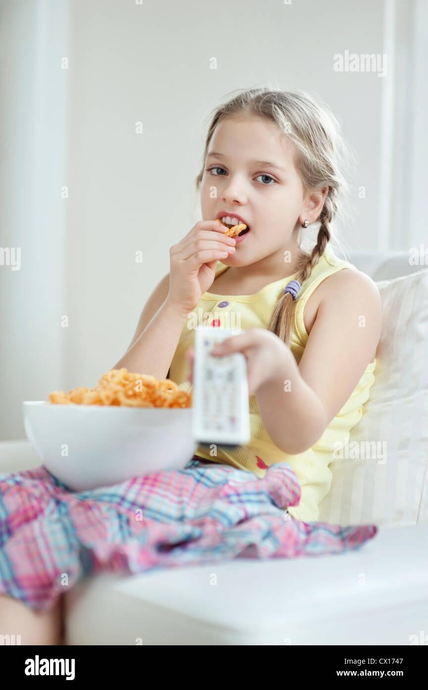 Little girl watching TV as she eats wheel shape snack pellets - Stock Image