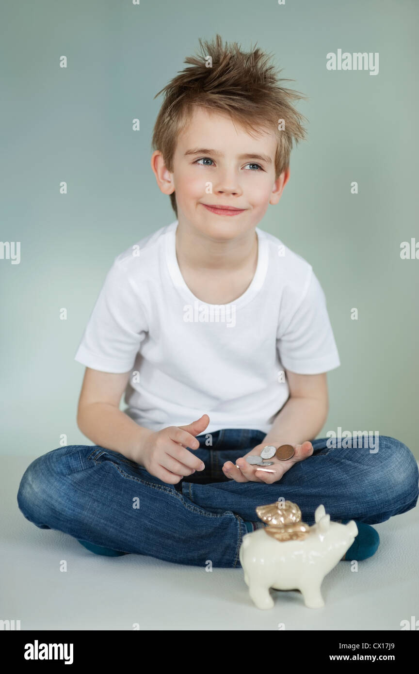 Thoughtful boy with piggy bank and coins over gray background - Stock Image