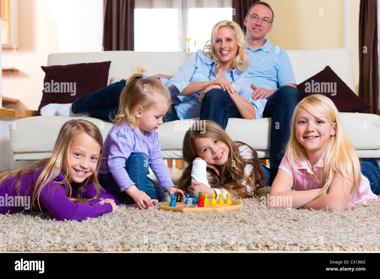 Family playing board game ludo at home on the floor Stock Photo