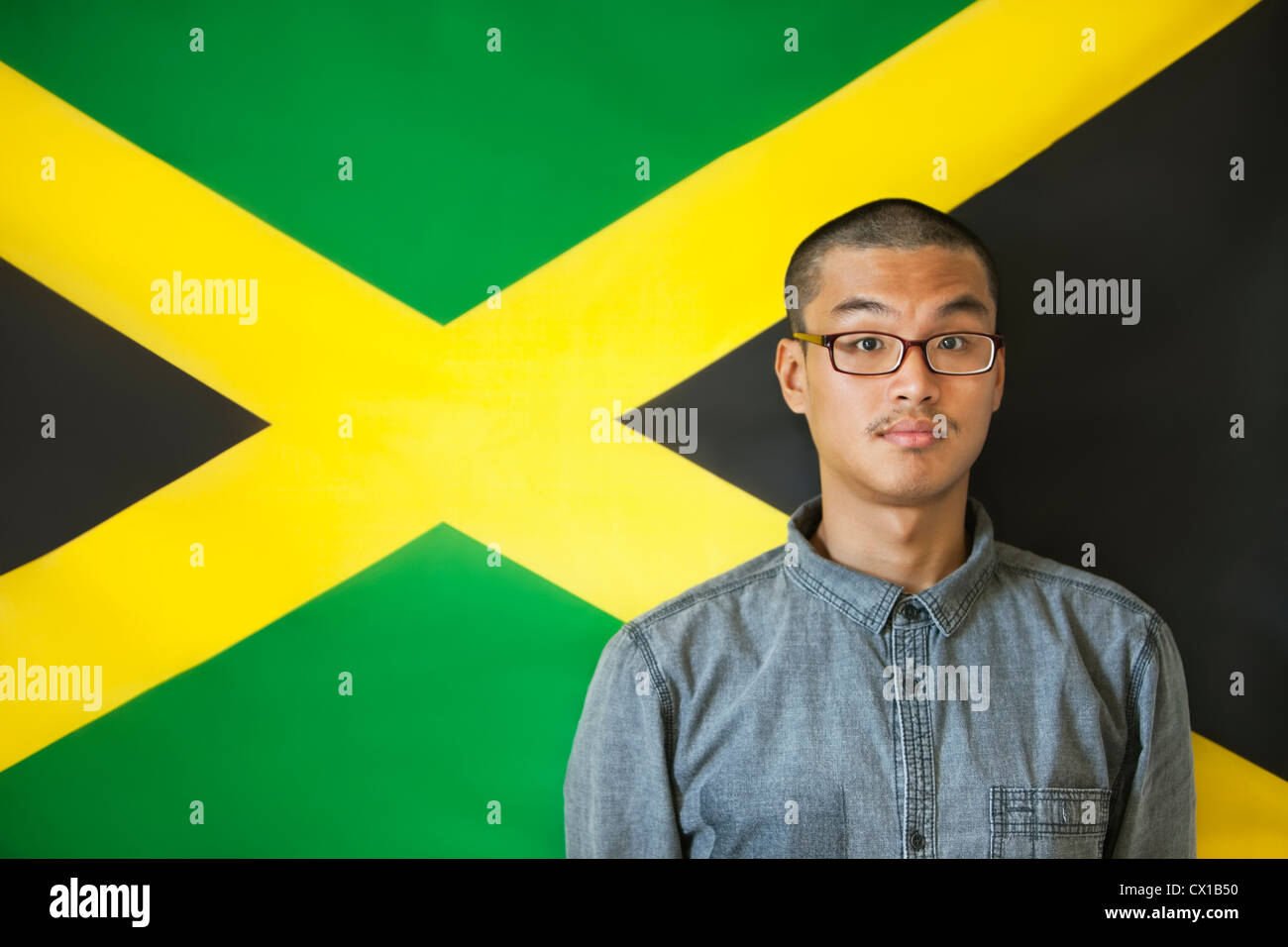 Portrait of a man with raised eyebrows against Jamaican flag - Stock Image