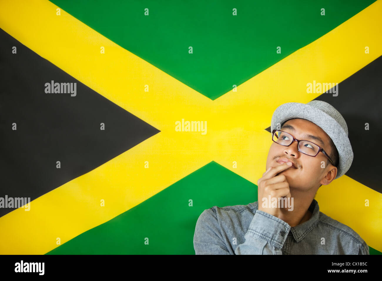 Thoughtful man against Jamaican flag - Stock Image