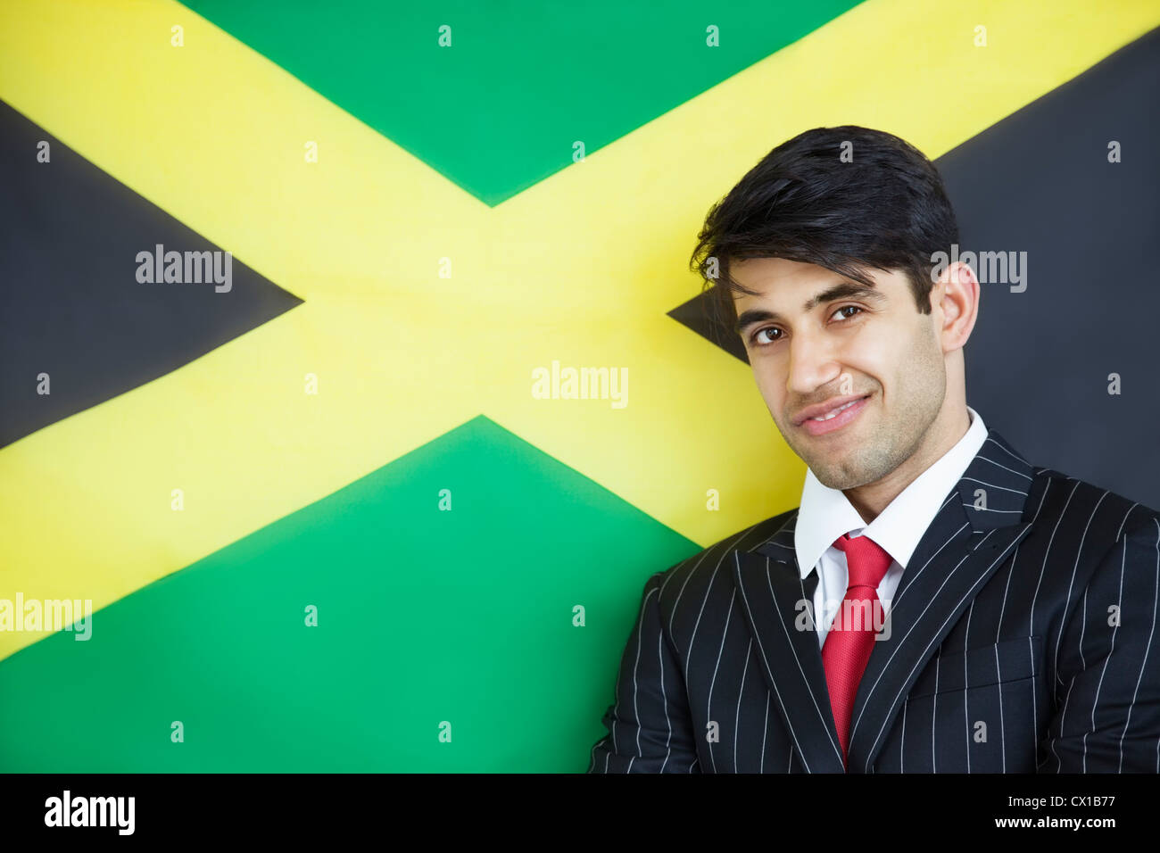 Portrait of a young confident businessman against Jamaican flag - Stock Image