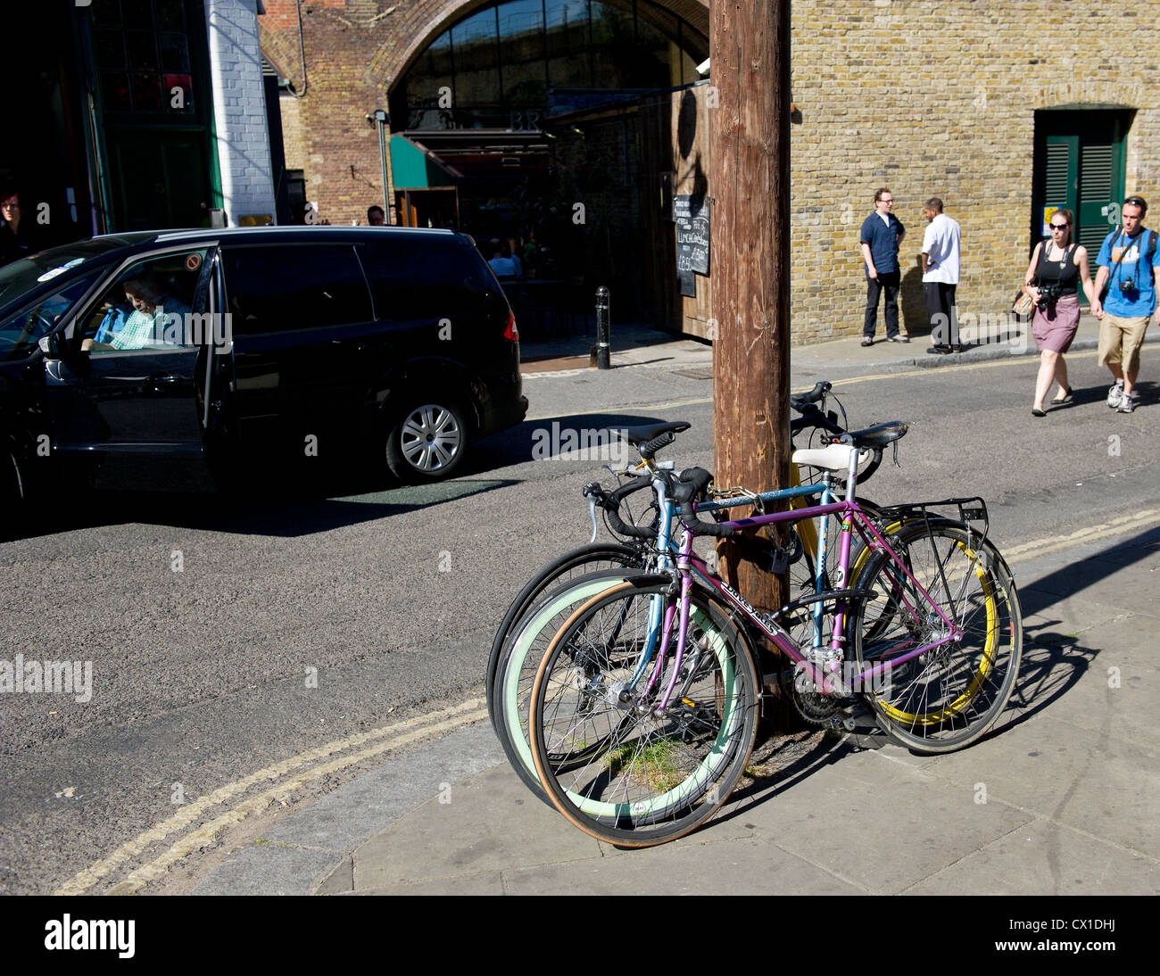 Bicycles secured to a wooden telegraph pole - Stock Image