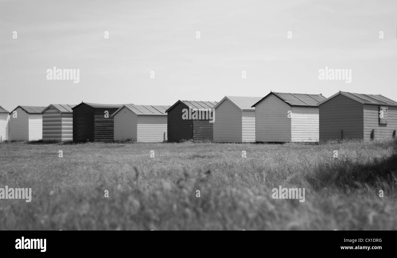Curving line of black and white beach huts on Hayling island sea front - Stock Image