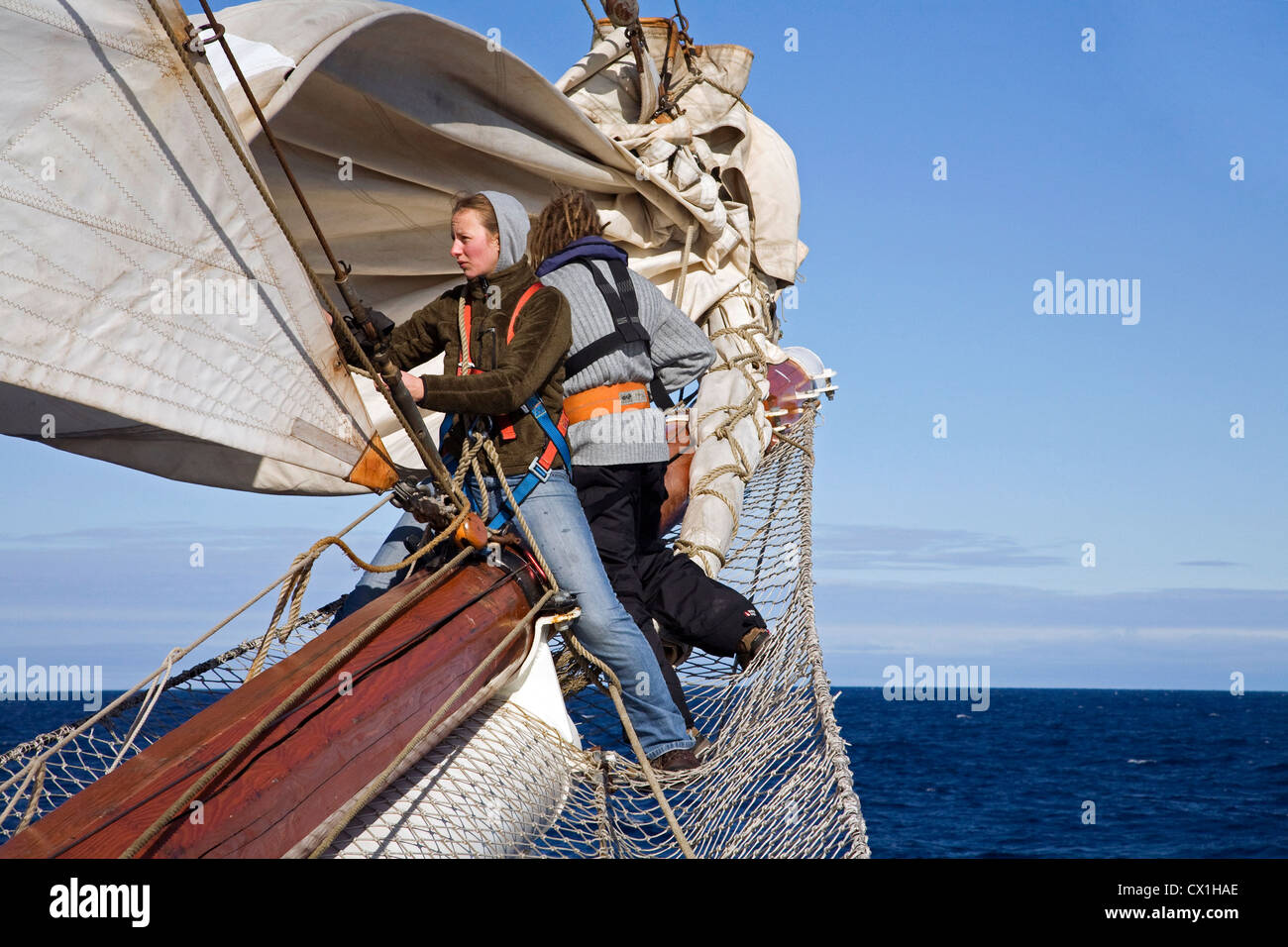 Sailors handling sails on bowsprit of the tall ship / barquentine Antigua sailing with tourists towards Svalbard, - Stock Image