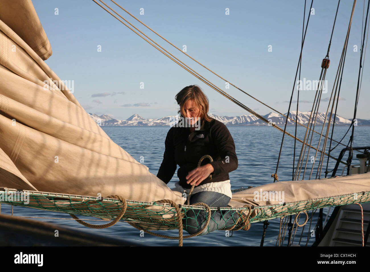 Sailor handling sail on deck of the tall ship / barquentine Antigua sailing with tourists towards Svalbard, Spitsbergen, - Stock Image