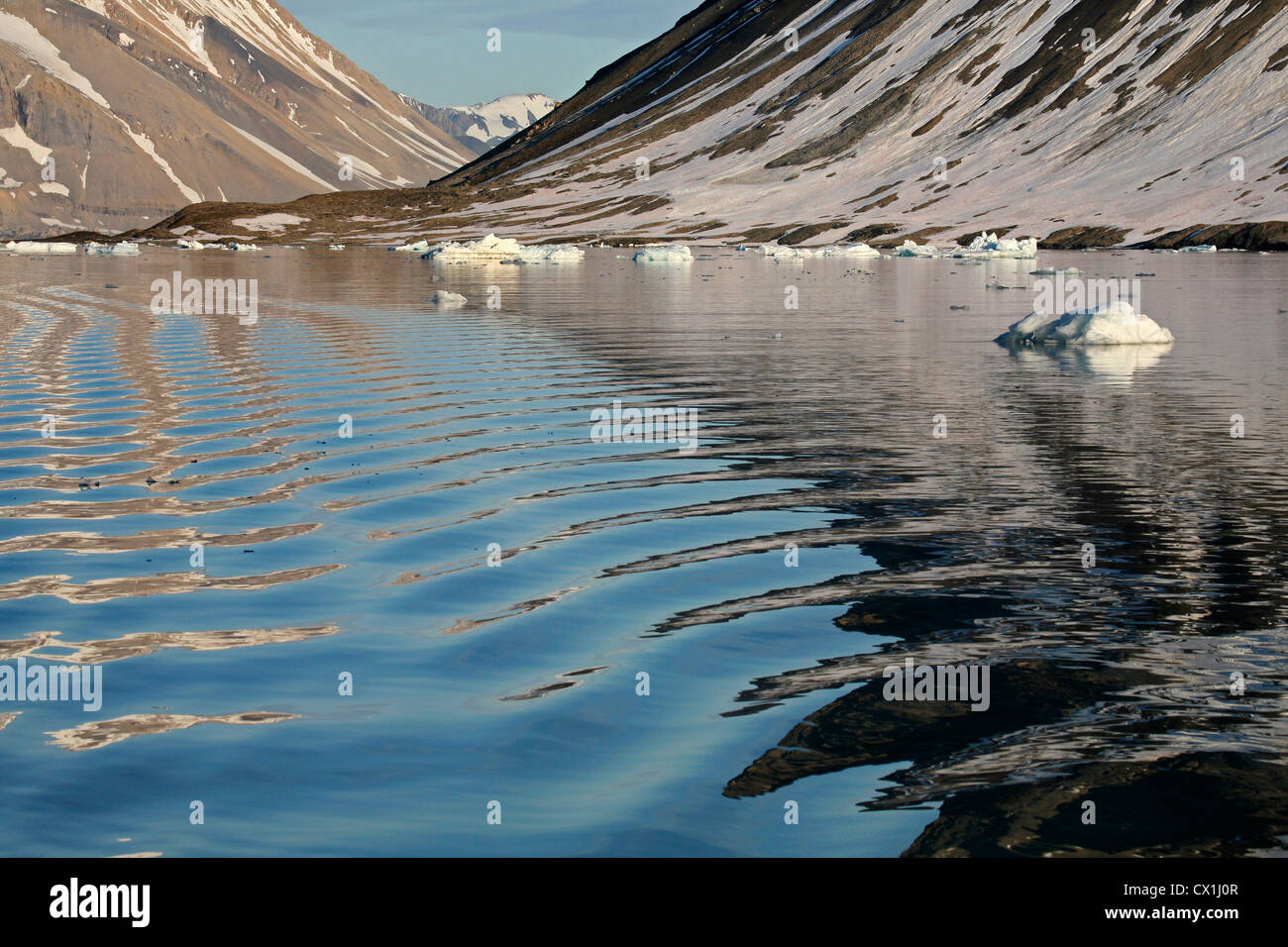 Water ripples in wake of sailing ship and view over mountains and sea at Svalbard, Spitsbergen, Norway - Stock Image