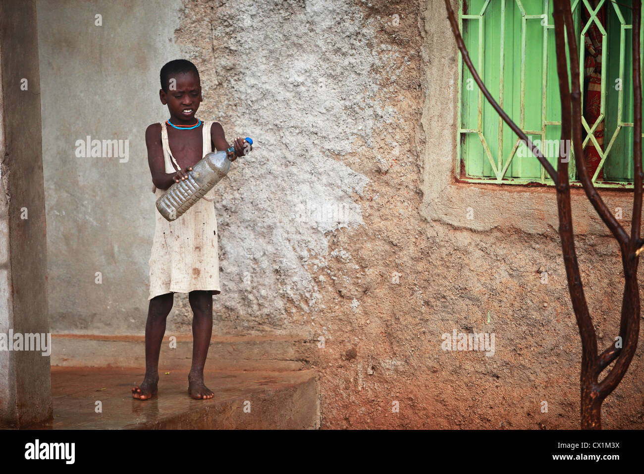 Young child trying to catch drops of rain in an empty bottle. - Stock Image