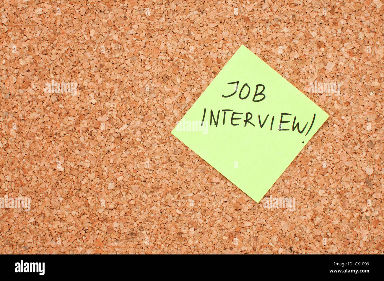 Job interview reminder note on a cork memory board - Stock Image