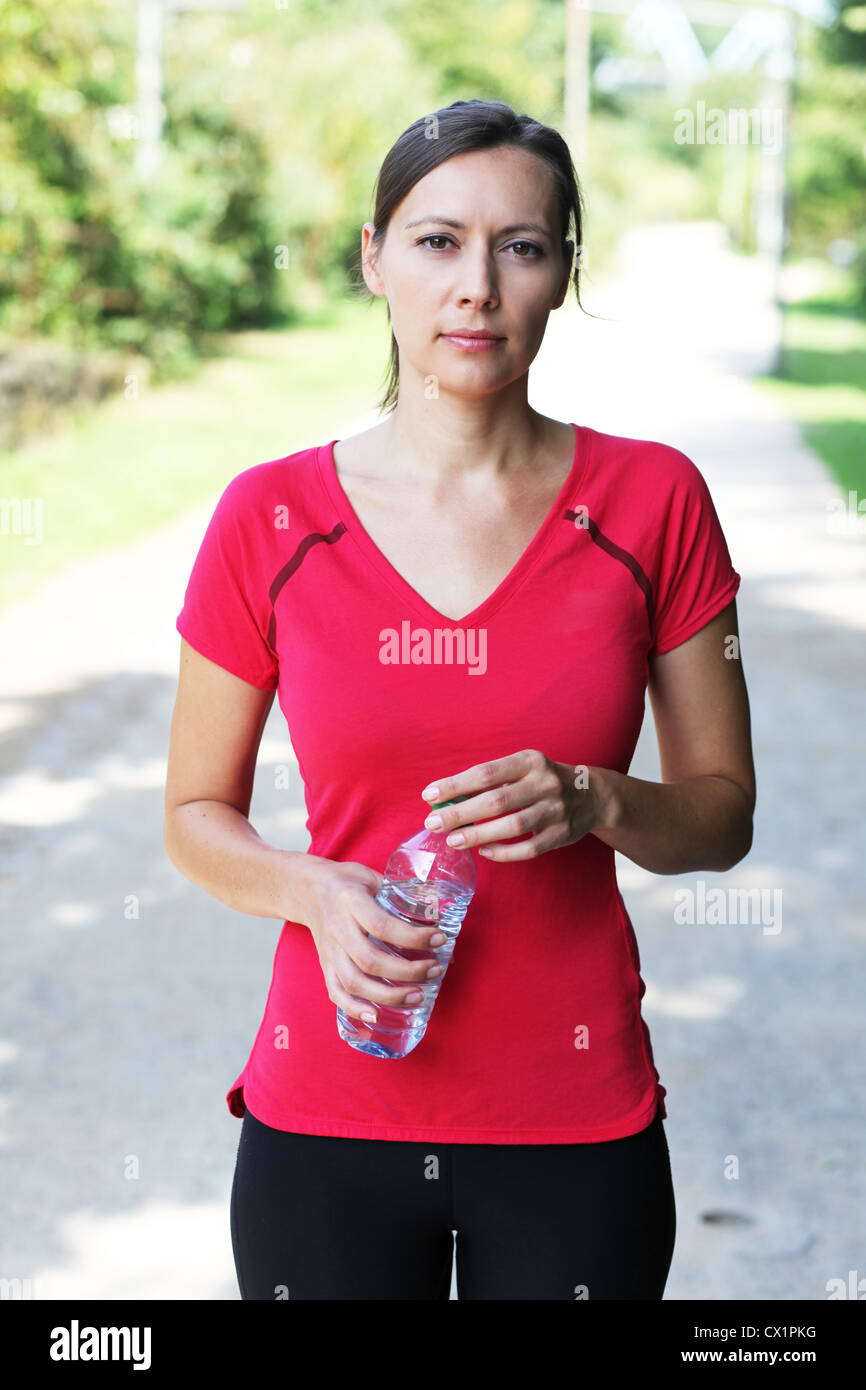 Woman with water bottle after running - Stock Image