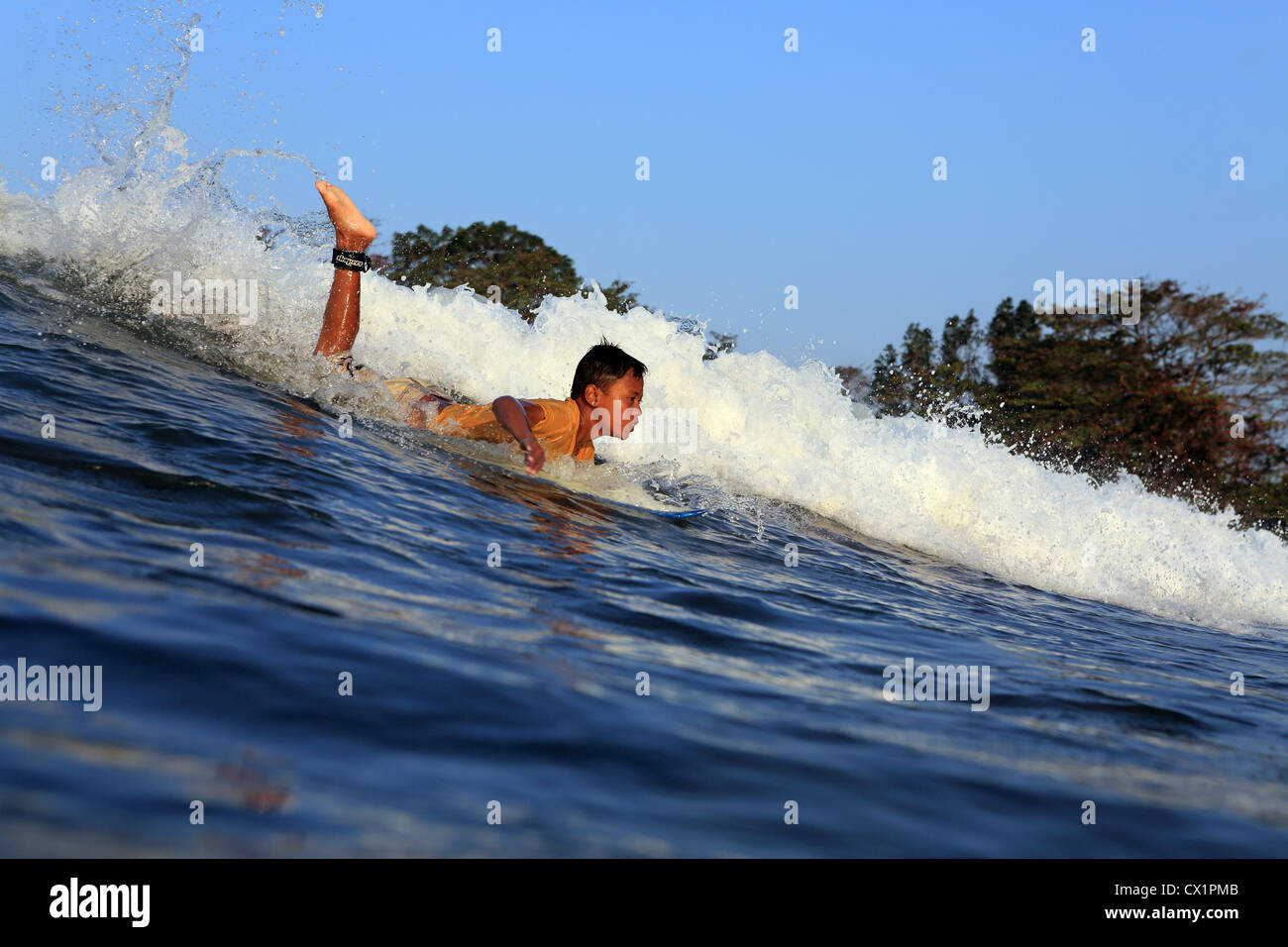 Young local boy surfing at Batu Karas in West Java, Indonesia. - Stock Image