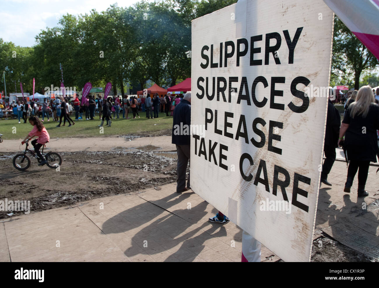 slippery surface signs due to Heavy rain days before that almost ruined the Newham Town show and carnival at  Central - Stock Image