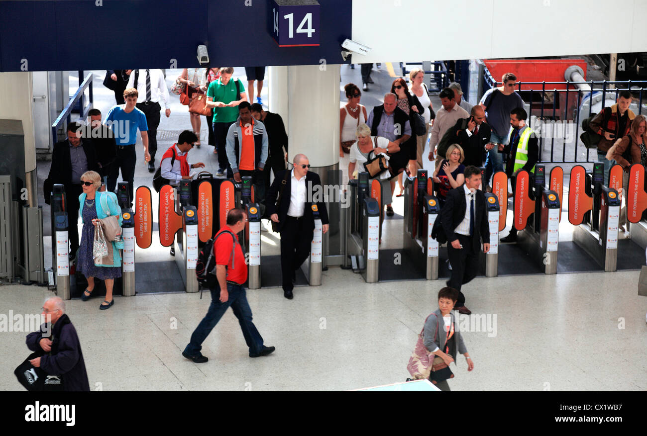Waterloo Station commuters at ticket barrier in London UK. - Stock Image