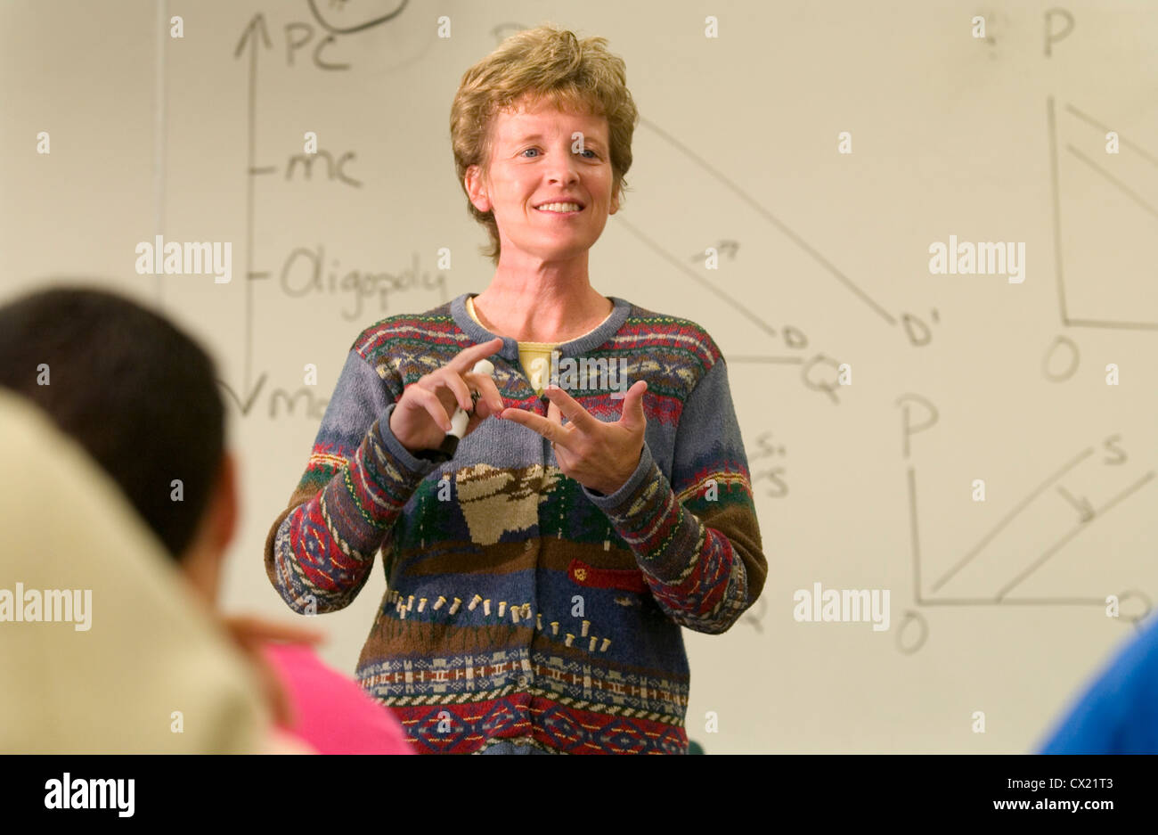 A female math teacher lectures in a college classroom. Stock Photo