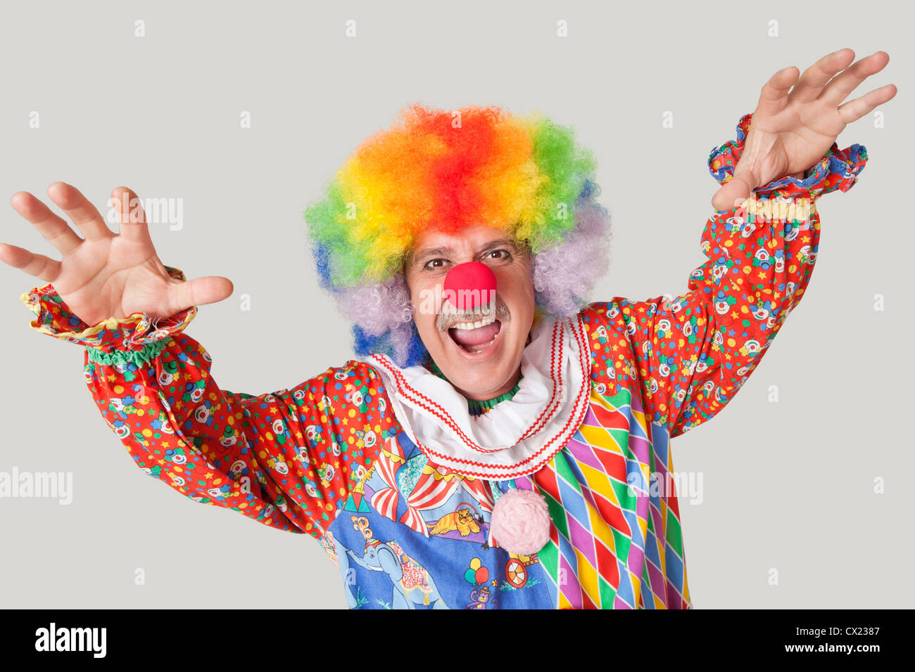 Portrait of funny clown with arms raised and mouth open against colored background - Stock Image