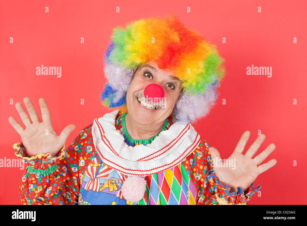 Portrait of funny clown with arms raised against colored background - Stock Image