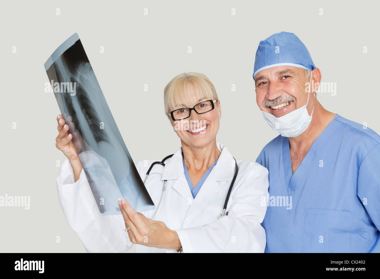 Portrait of happy medical colleagues with radiograph over gray background - Stock Image