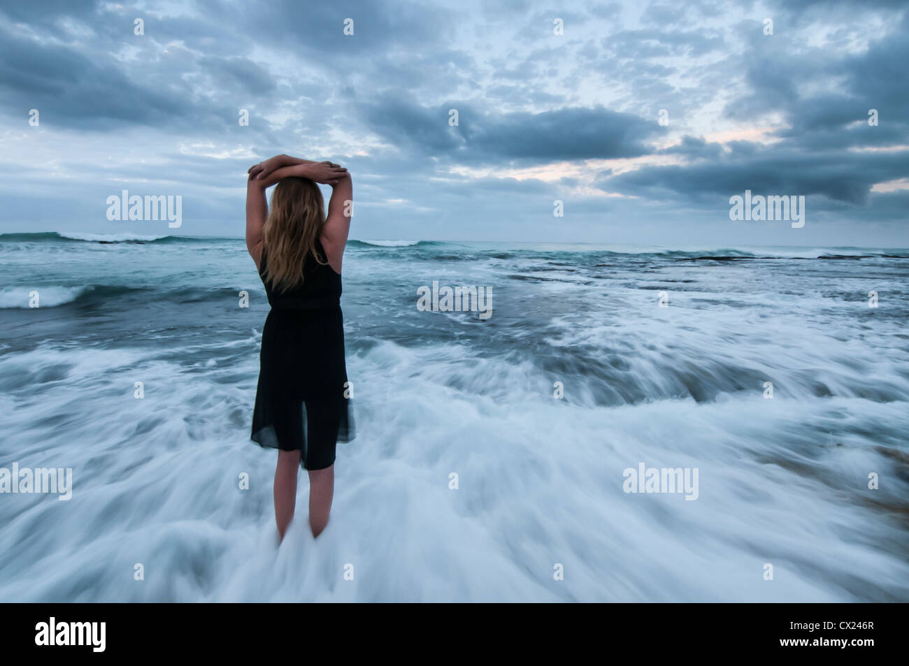 girl holding her arms above her head while water washes over her feet - Stock Image
