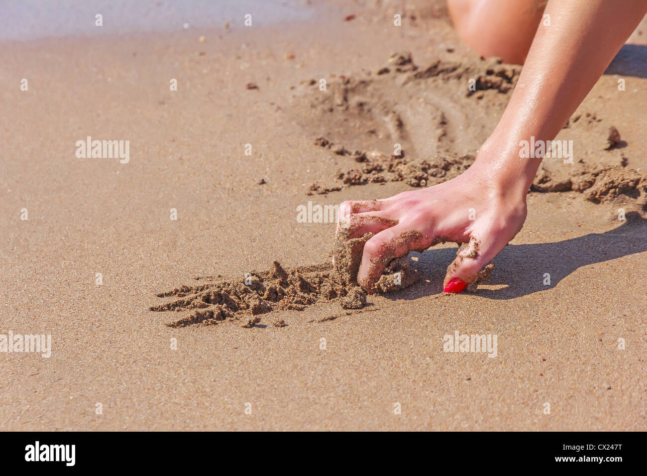 Hand of a young woman with red nails scratching the sand Stock Photo ...