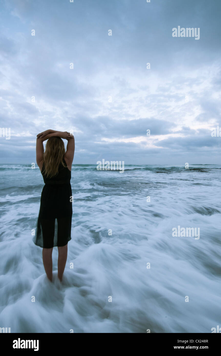 Girl standing on rocks with waves washing in slow motion over her feet whilst appearing to be in thought - Stock Image