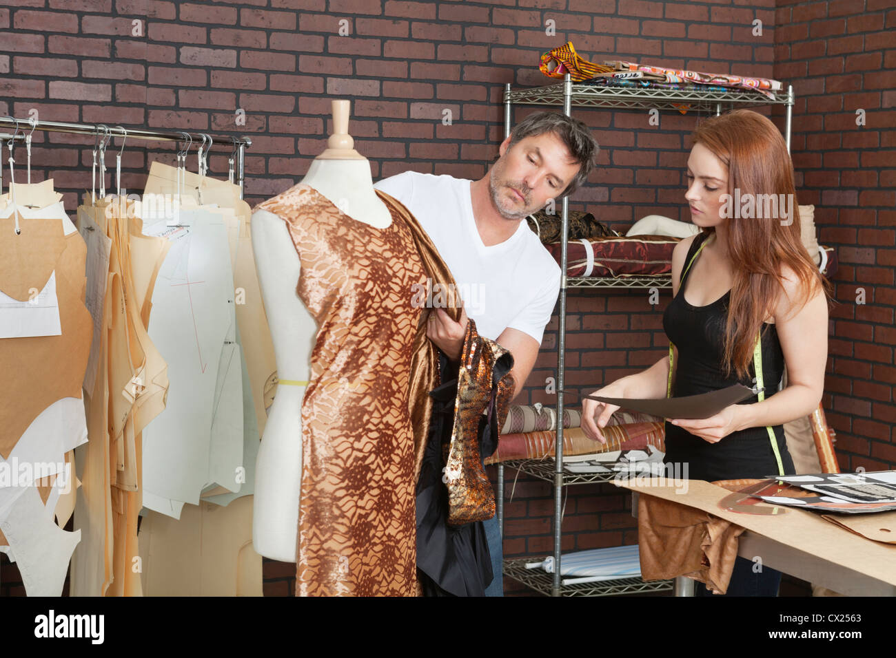 Fashion designers working together on an outfit in design studio - Stock Image