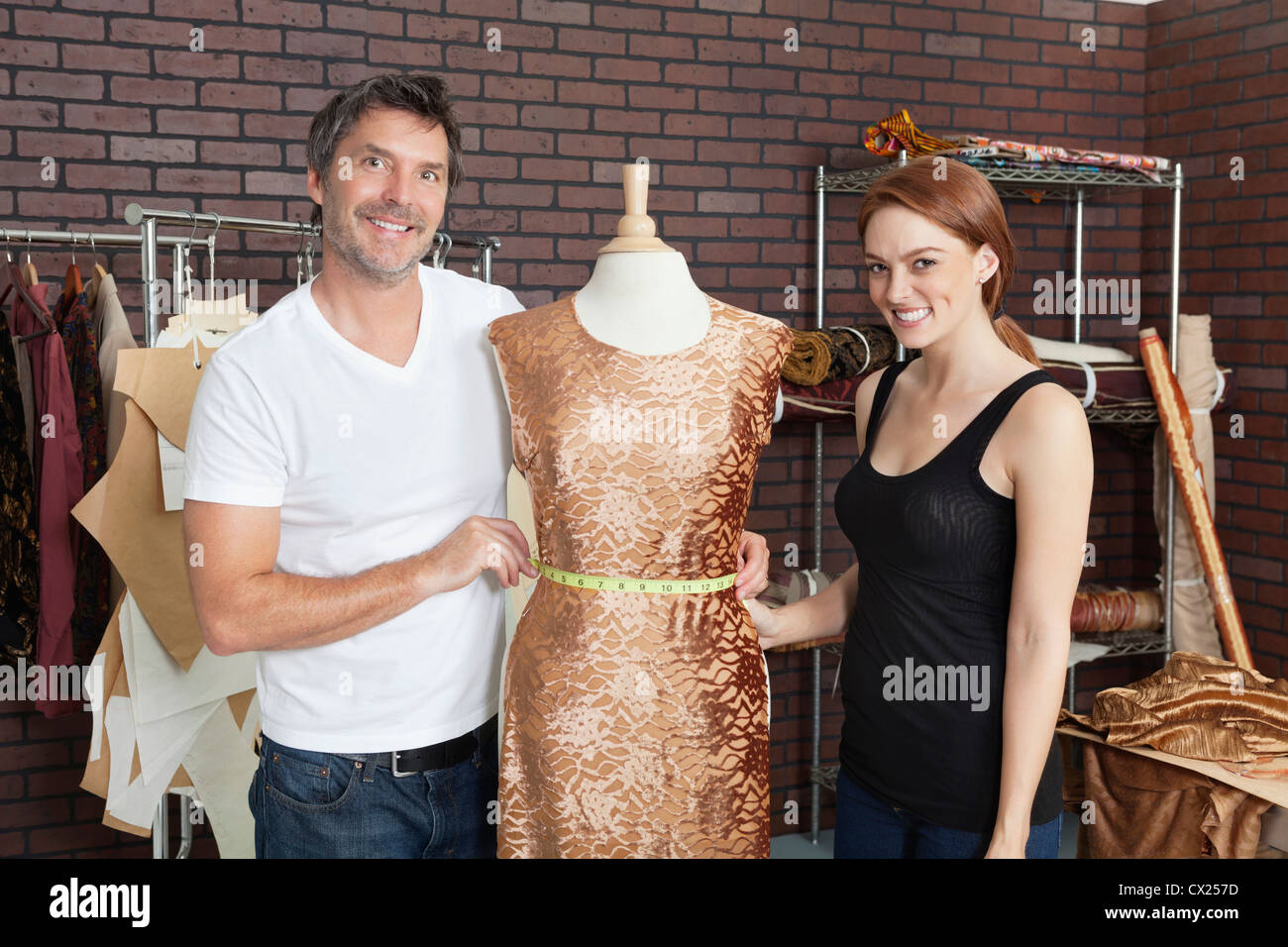 Portrait of fashion designers working together on an outfit in design studio - Stock Image