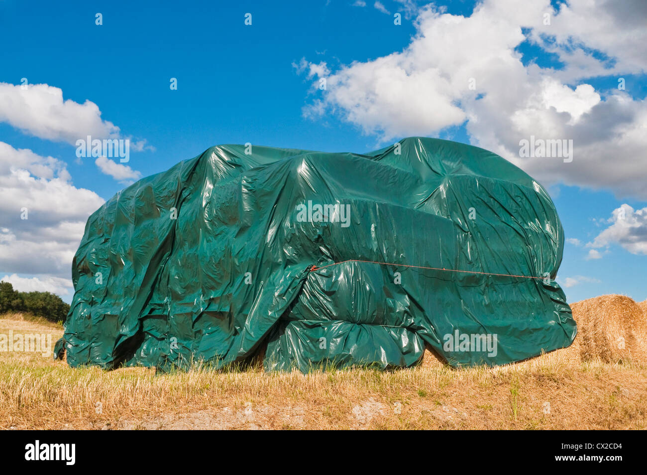 Stack of straw bales covered in plastic protective sheeting - sud-Touraine, France. - Stock Image
