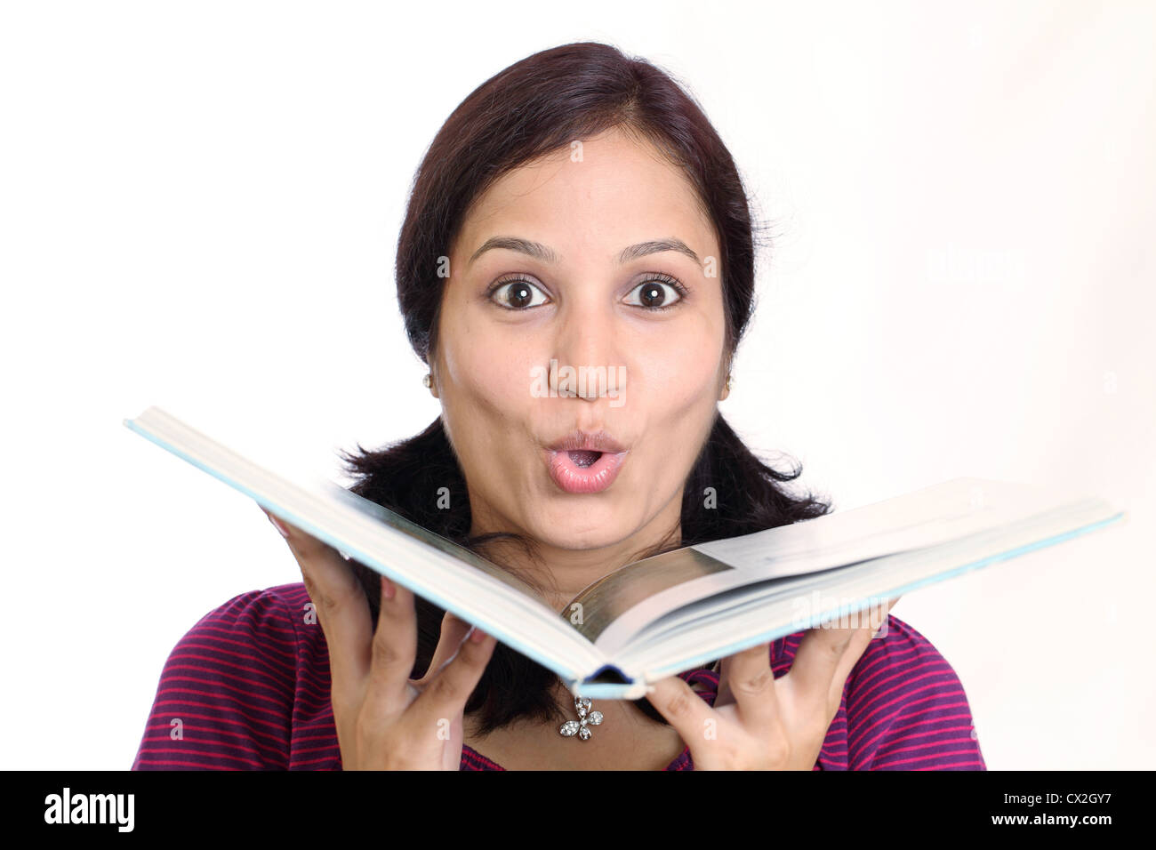 Young Indian female student looking over book - Stock Image