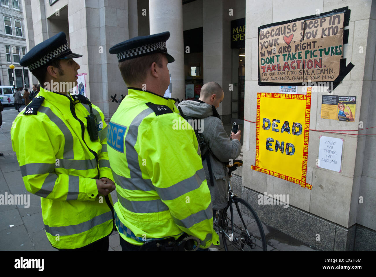 TWO POLICE OFFICER LOOKING AT THE WALL READING THE ANTI CAPITALIST  PUBLIC INFORMATION - Stock Image
