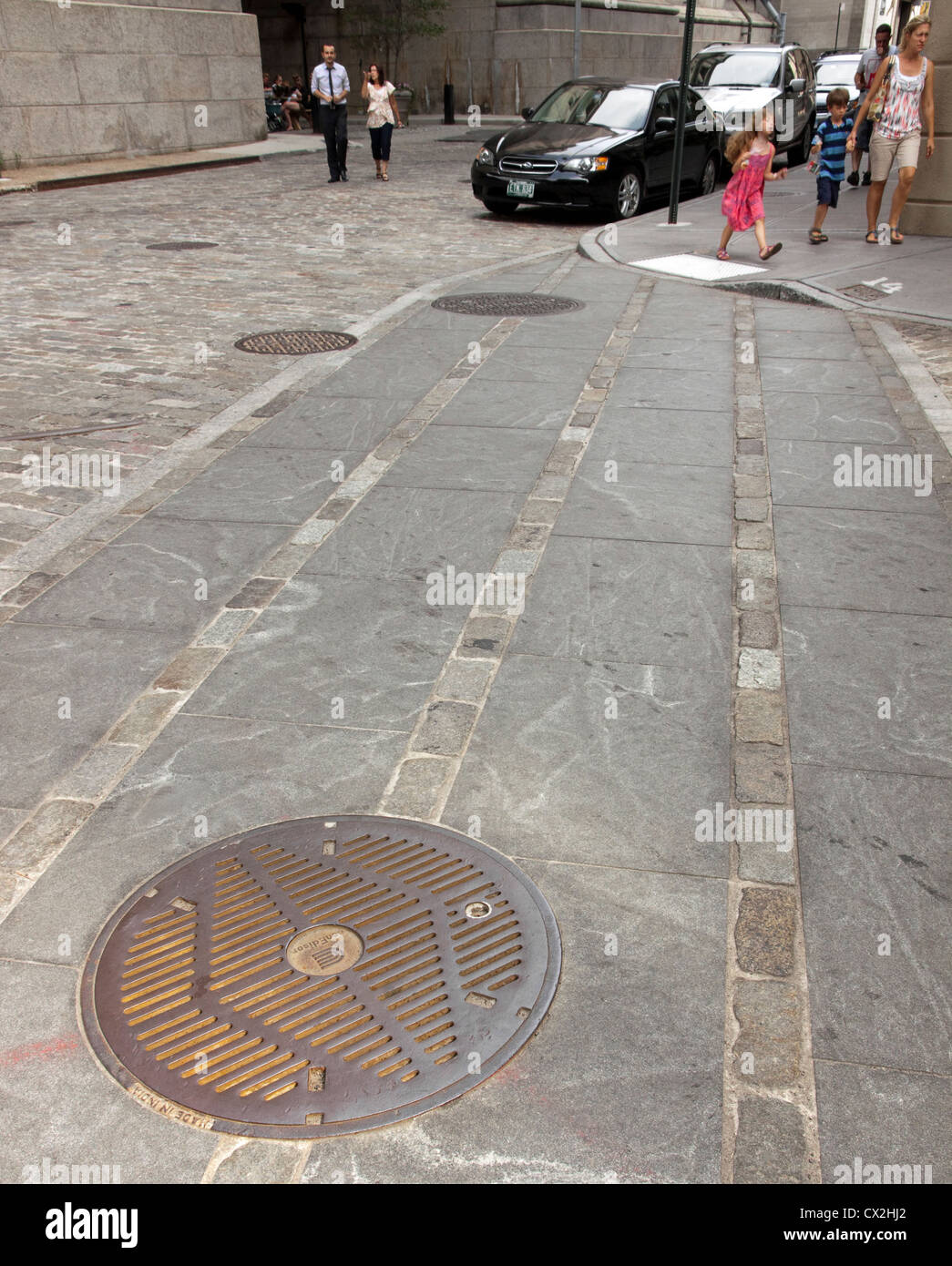 People walking the streets of DUMBO, Brooklyn, New York, nearby a manhole cover. - Stock Image