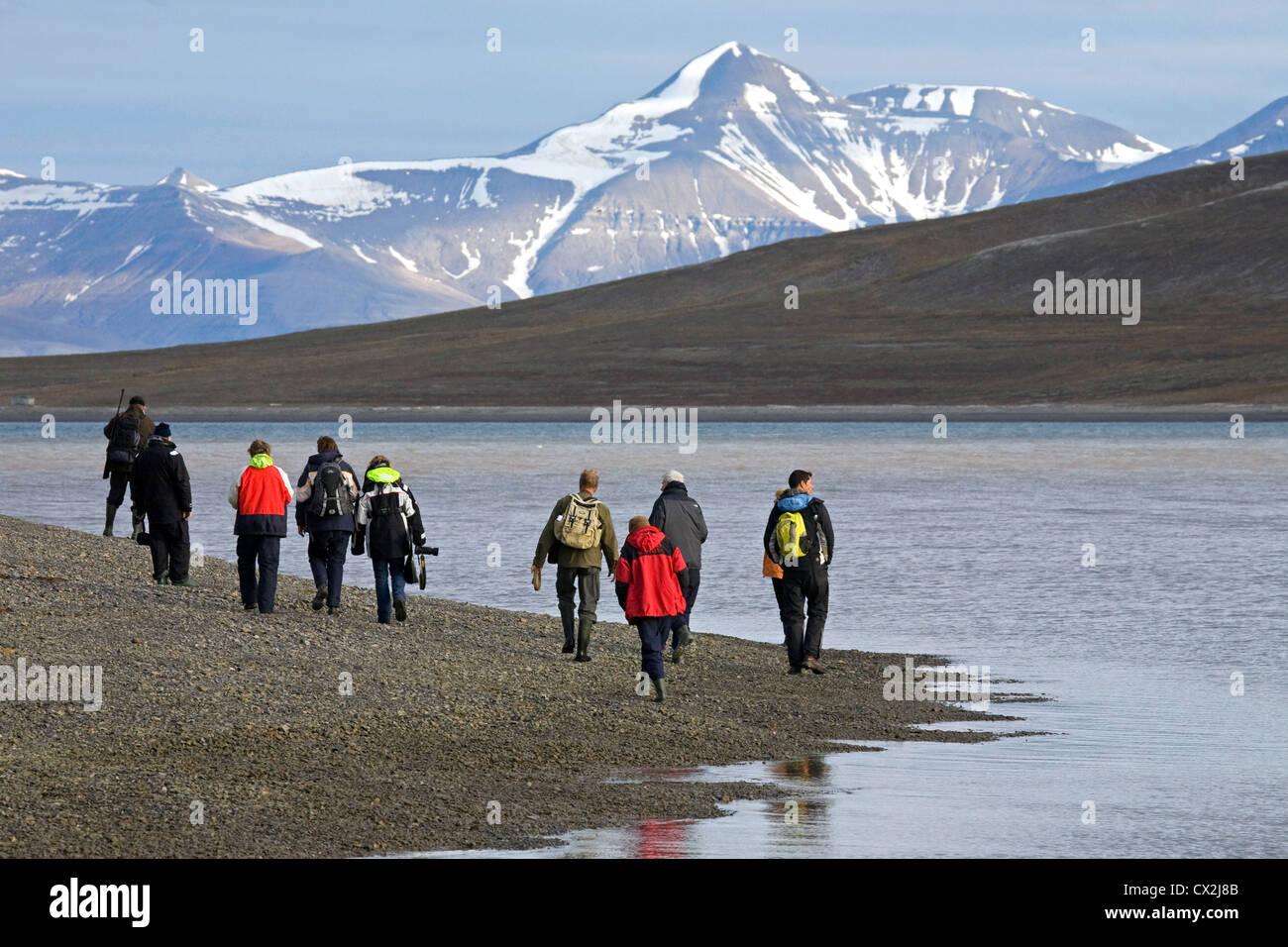 Tourists walking on beach along Tempel Fjord with guide armed with rifle against polar bears in Svalbard, Spitsbergen, - Stock Image