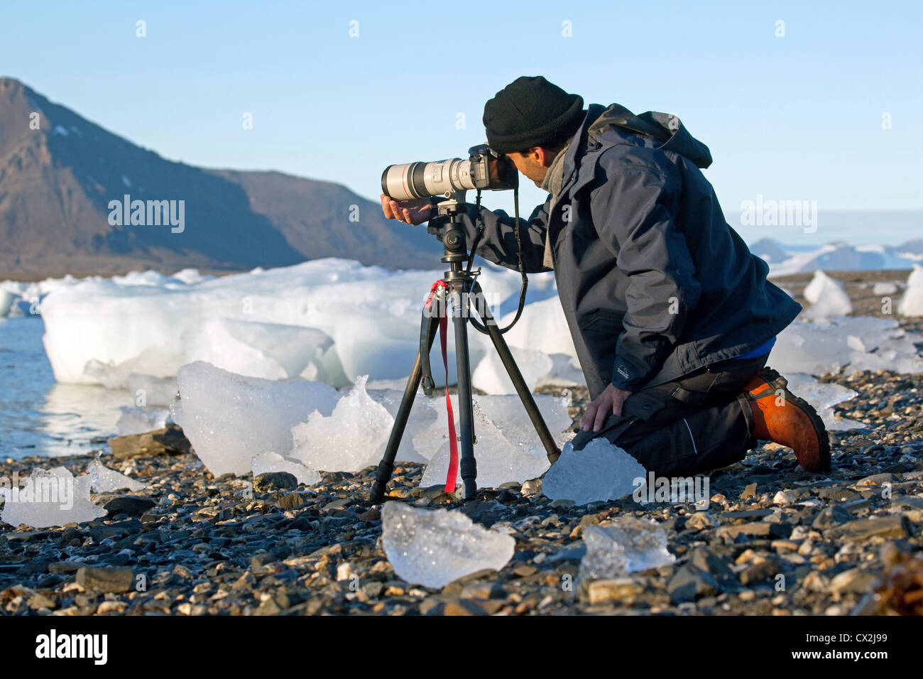 Wildlife / nature photographer taking pictures with long telephoto lens on tripod in the Arctic at Svalbard, Spitsbergen, - Stock Image