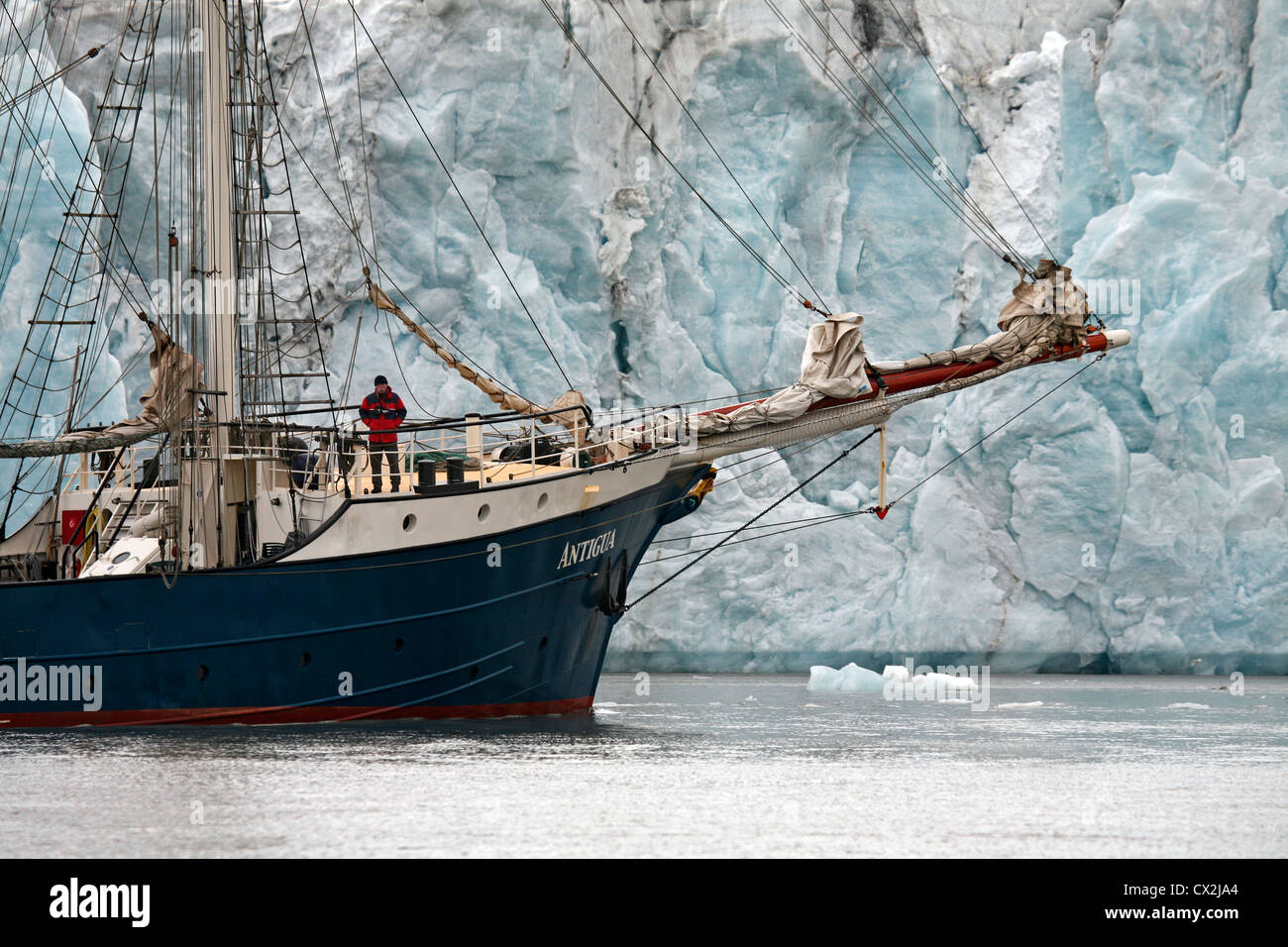 The tall ship / barquentine Antigua sailing with tourists along glacier at Svalbard, Spitsbergen, Norway - Stock Image