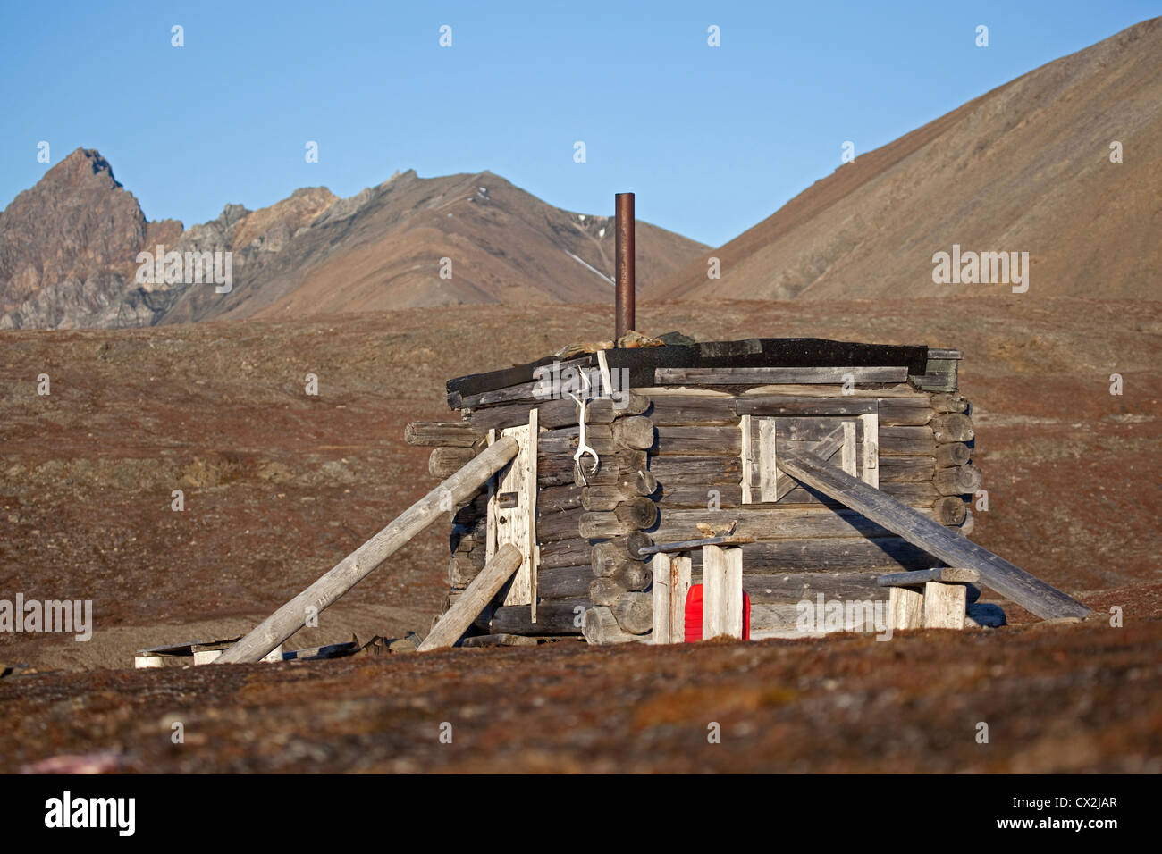 Wooden hunting log cabin tightly shut, barricaded with heavy logs against raiding polar bears on Svalbard, Spitsbergen, - Stock Image