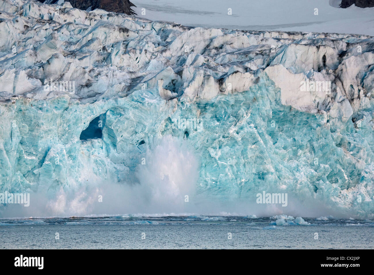 Large chunk of ice breaking off glacier and tumbling with big splash in the Magdalenefjord on Svalbard, Spitsbergen, - Stock Image