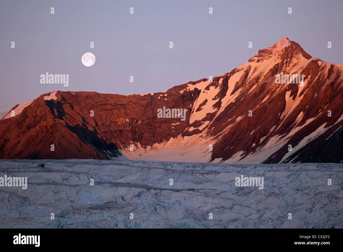 Full moon rising over glacier and mountains at Svalbard, Spitsbergen, Norway - Stock Image
