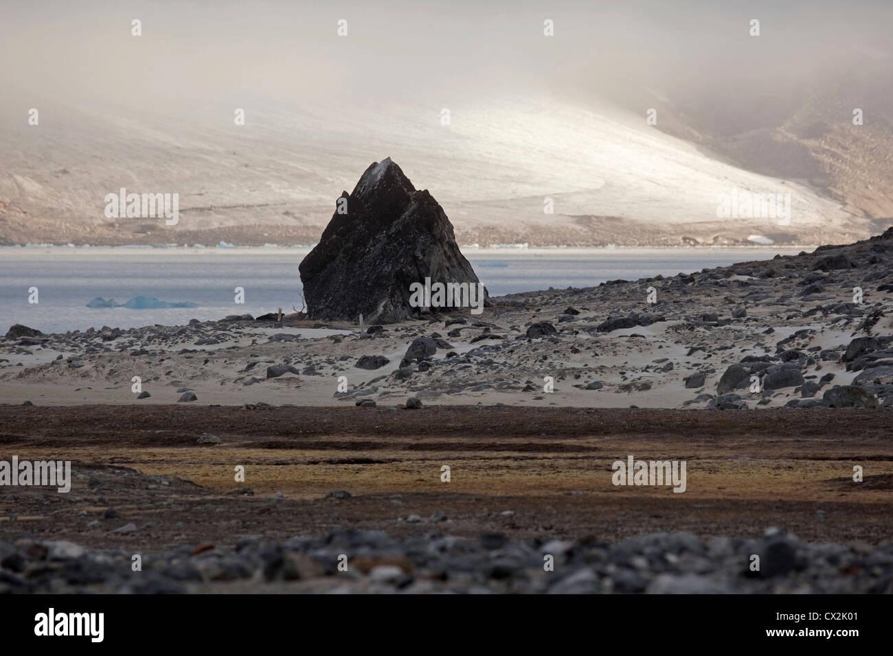 Large granite boulder on beach along the Magdalenefjord on Svalbard, Spitsbergen, Norway - Stock Image
